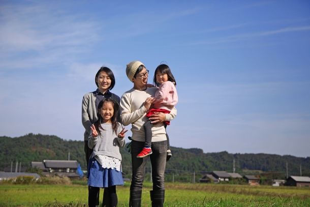 プロジェクト提案者の原田一家と、空の大きな高島市の田園風景