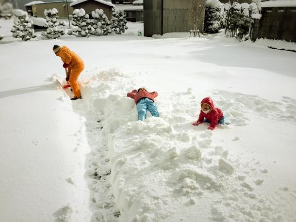 家の前を雪かきする僕と、雪と戯れる娘たち
