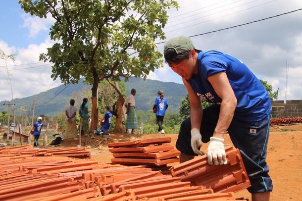 屋根の瓦を運ぶチームメイト