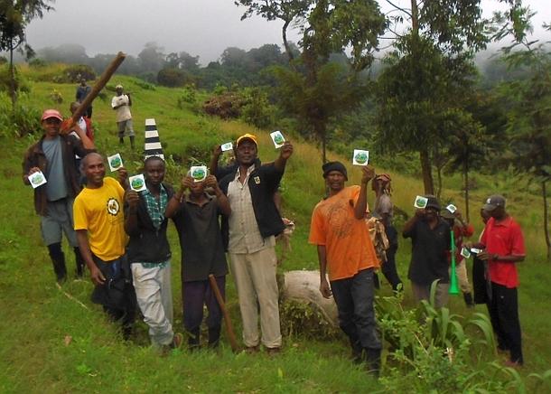"""誇らしげにステッカーを掲げる""""エデンの森""""で植林中の村人たち。彼らの背後には国立公園公社が設置したビーコン(白黒の縞模様)が写っています。"""