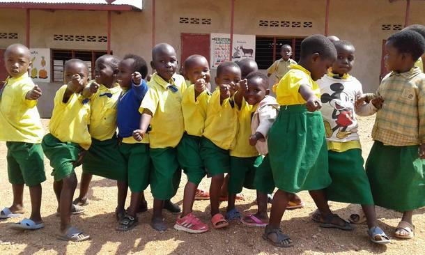 支援予定の校舎の前でポーズを決める園児たち