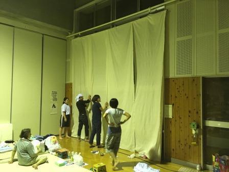 朝倉市内の避難所で避難生活を送っている若者たちと一緒に日除けカーテンを設置