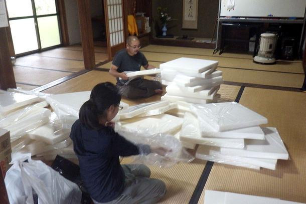 お寺の本堂で座布団を詰める作業の様子