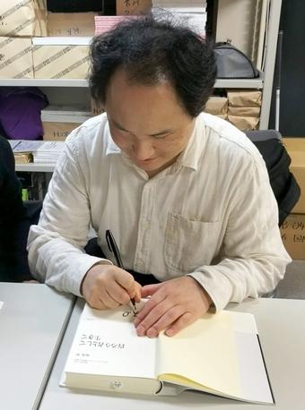 書籍にサインをしている福島理事