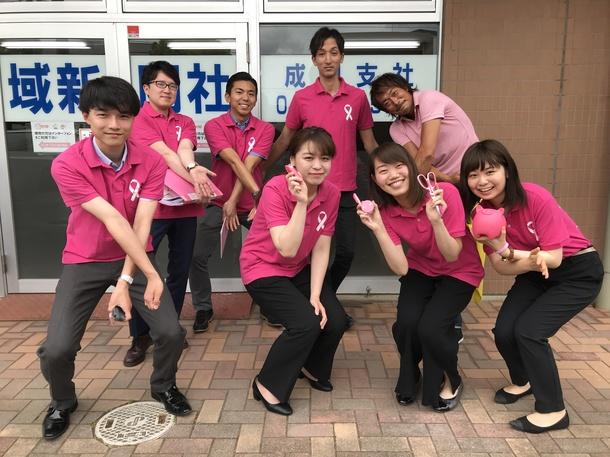 ピンクリボン運動のポロシャツを着て営業する地域新聞社成田支社の社員