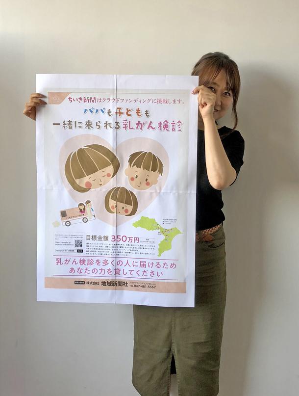地域新聞社のピンクリボン運動として行っている乳がん検診実施のためのクラウドファンディングポスターを持つ社員