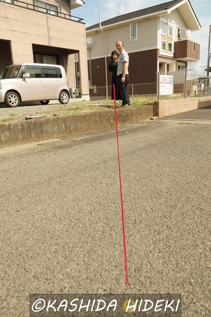 秋山さんのご自宅。手前の黄色い杭(リニアルートの北端)から赤い線に沿って、リニアの高架が設置される。これでは家屋は一日中日陰になる。