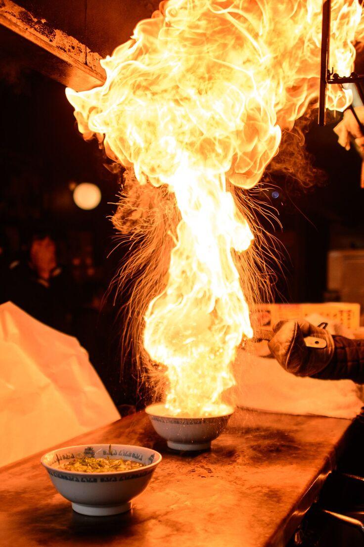炎が上がるラーメンの様子